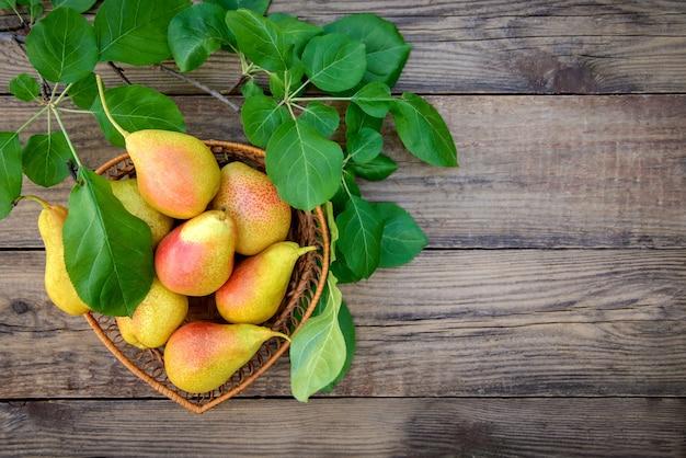 Урожай спелых желто-красных груш в плетеной посуде на деревянном фоне с копией пространства