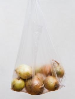 灰色の背景上の透明なビニール袋に収穫玉ねぎ