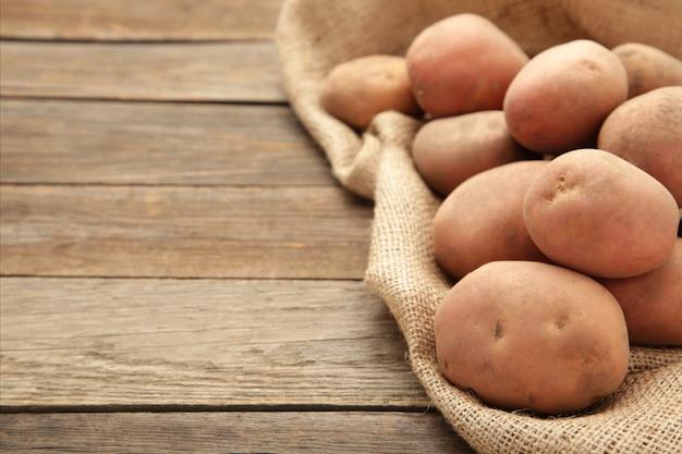コピースペースを持つ素朴な背景に黄麻布の袋でジャガイモを収穫します。