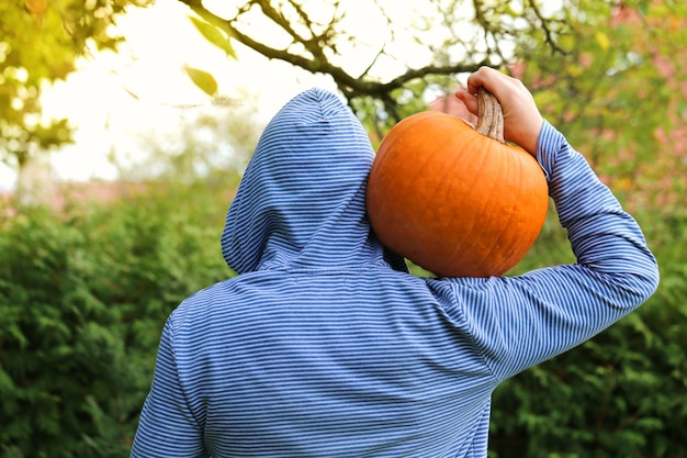 Harvest of pumpkins.a man with orange pumpkin on his shoulder on a blurred green background. thanksgiving day.