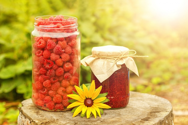Harvest raspberry berries in the glass jar, jam and flower on old stump, sunny summer day vegetable garden village