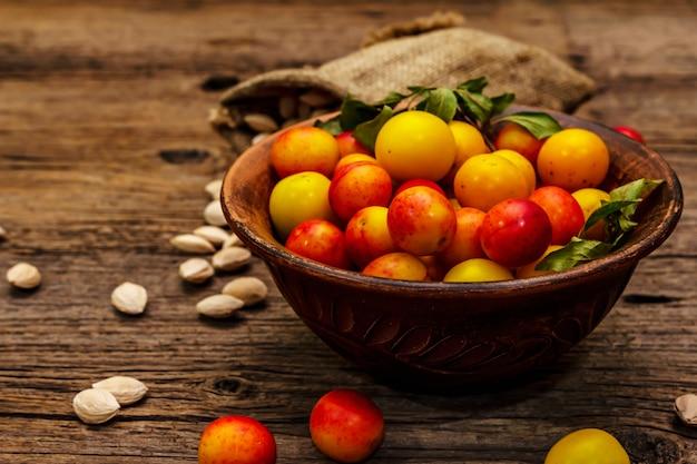 熟したチェリープラムを収穫します。フルーツ盛り合わせと種子を袋に詰めたもの。古い木の板の背景、クローズアップ