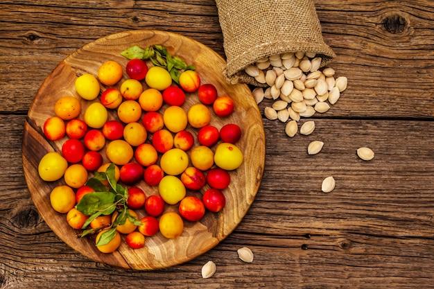 熟したチェリープラムを収穫します。フルーツ盛り合わせと種子を袋に詰めたもの。古い木の板の背景、トップビュー