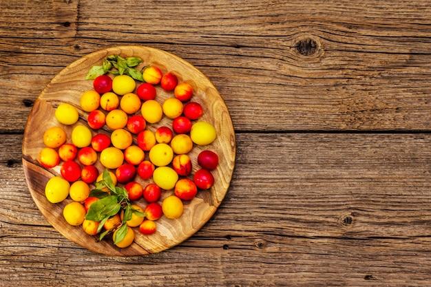 熟したチェリープラムを収穫します。フルーツ全体と新鮮な葉の盛り合わせ。古い木の板の背景、トップビュー