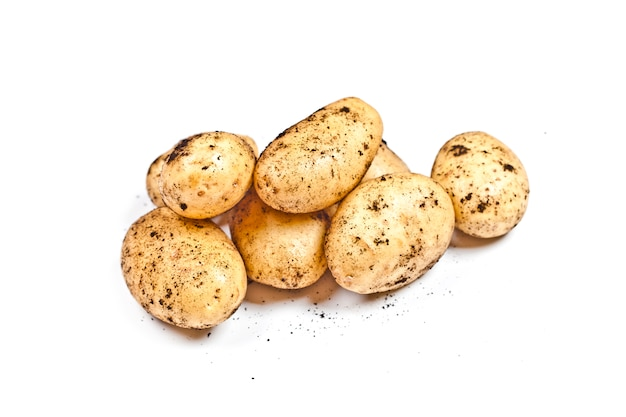 Harvested dirty potatoes heap isolated on white