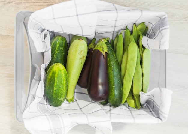 Harvested fresh vegetables in the container with napkin