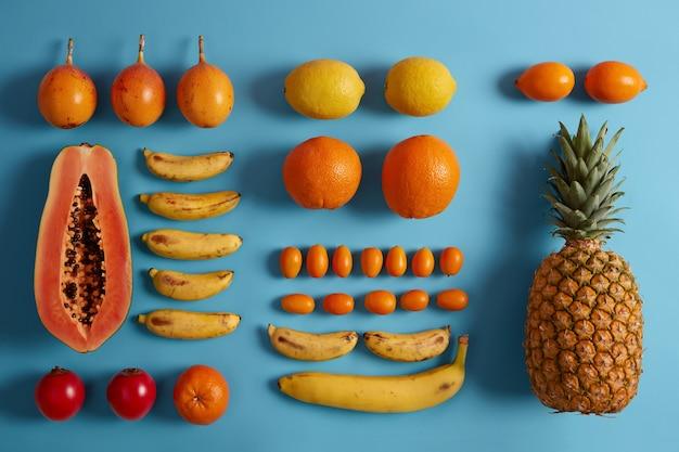 青い背景に収穫されたジューシーな熱帯のエキゾチックなフルーツ。パパイヤ、レモン、バナナ、パイナップル、キンカン、タマリロの品揃え。スムージーを作るための材料。健康的なベジタリアン有機食品