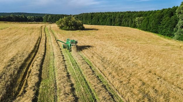 上からフィールド空撮で働く収穫機、熟した小麦畑を収穫する収穫機農業機械