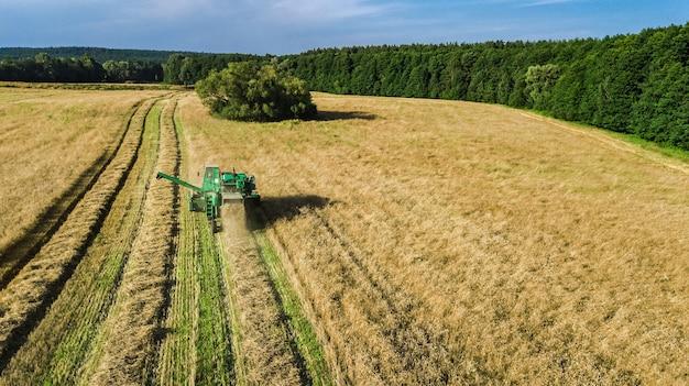 上から空中写真で作業する収穫機、熟した小麦畑を収穫するコンバイン農業機械