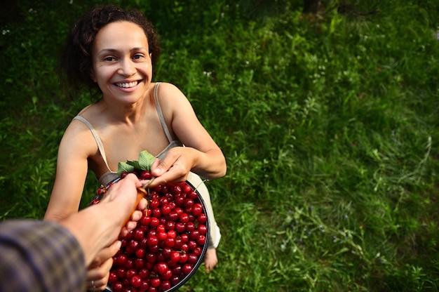 カントリーハウスの庭でサクランボを収穫します。脚立の男は、リネンのドレスを着た魅力的な笑顔のアフリカの女性にさくらんぼのバケツを提供しています