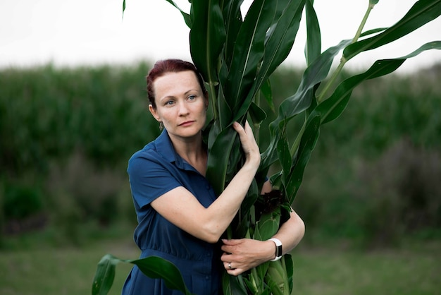 トウモロコシの収穫、畑で作物を持っている女性