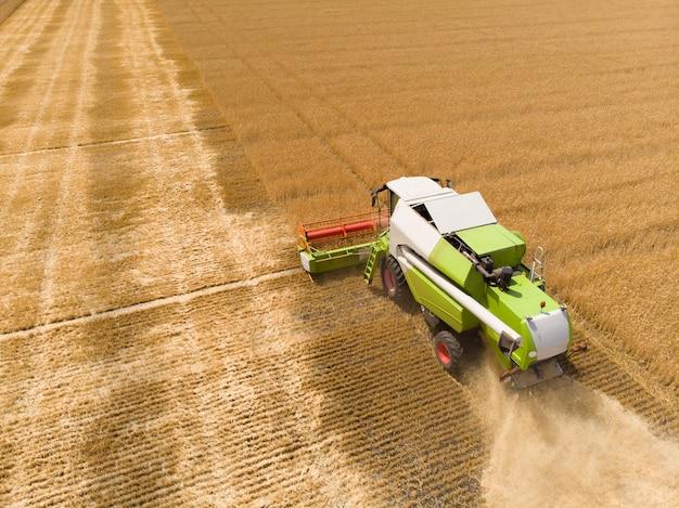 Уборка пшеницы летом зерноуборочный комбайн сельскохозяйственная машина собирает золотую спелую пшеницу на поле зрения сверху