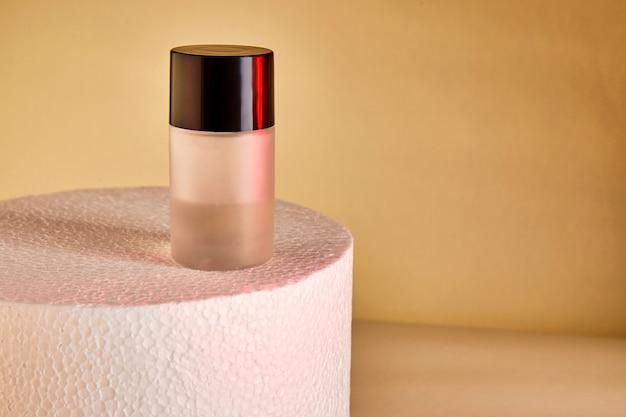 白い表彰台にラベルのない香水瓶を収穫する。