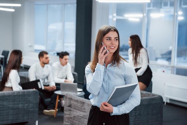 契約があります。バックグラウンドで従業員とオフィスに立っている若い女の子の肖像画