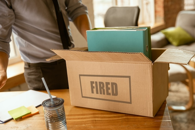 彼のオフィスの持ち物を梱包し、新しい労働者のために職場を離れなければなりません。