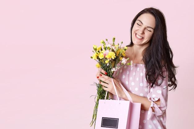 Крупным планом портрет привлекательной темноволосой молодой женщины в платье, любит приходить весна, любит получать цветы и подарки от ее hasband, радостно прищурить глаза. люди, подарки, концепция празднования.