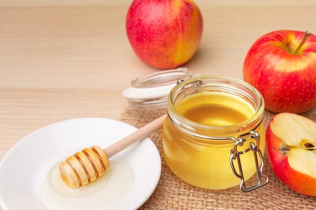 ユダヤ人の休日ロッシュhashanah背景に蜂蜜、木製のテーブルの上のリンゴ。