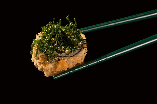 Hashi hold sushi and rolls isolated over black background