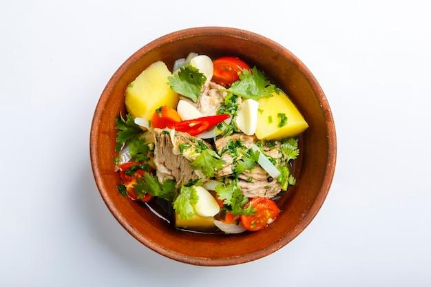 점토 판에있는 hashlama. 재료 쇠고기 갈비, 감자, 허브, 마늘. 흰색 배경에. 평면도