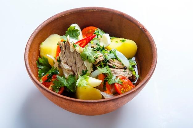 점토 판에있는 hashlama. 재료 쇠고기 갈비, 감자, 허브, 마늘. 흰색 배경에