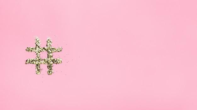 Хэштег из блесток на розовом фоне.