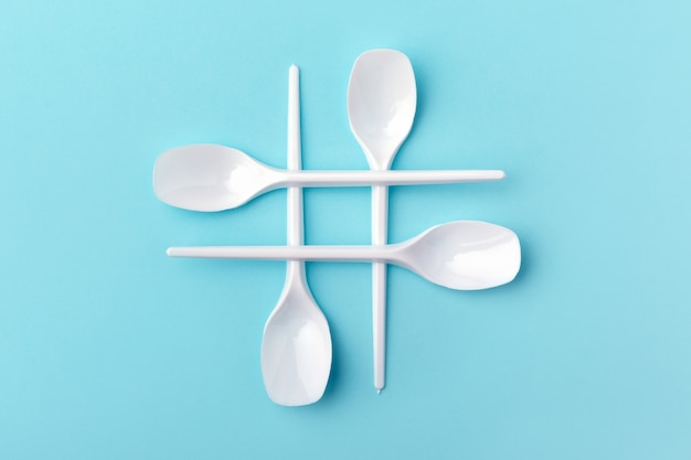 Hashtag made of white plastic spoons on blue background. concept of ecology problem.