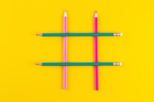 Знак хэштега из скрещенных красочных карандашей на желтой поверхности