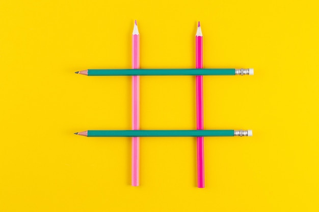 Hashtag sign from crossed colorful pencils on yellow surface