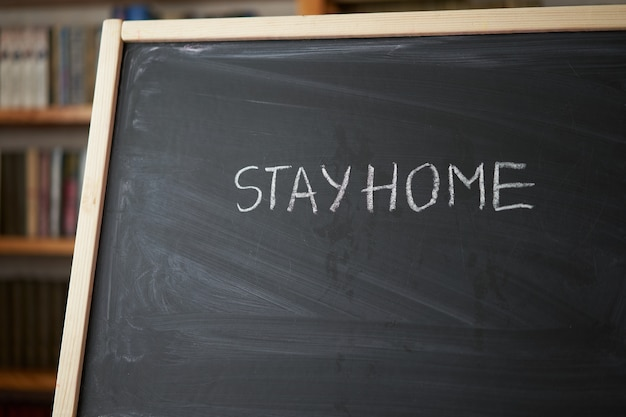 Hashtag stay at home. outbreak warning. written white chalk on blackboard in connection with epidemic of coronavirus worldwide. covid 19 pandemic text on black background with free space.