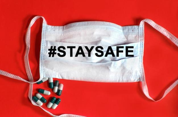 ハッシュタグstaysafe-保護フェイスマスクのテキスト、赤い背景のタブレット