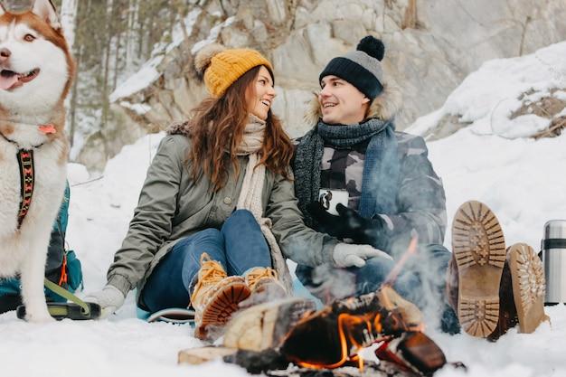 寒い季節に森林自然公園で犬haskiと幸せなカップル。旅行冒険ラブストーリー