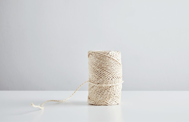 Hasp of craft rope isolated in center of white table , side view.