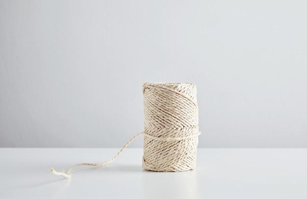 Hasp di corda artigianale isolata al centro del tavolo bianco, vista laterale.
