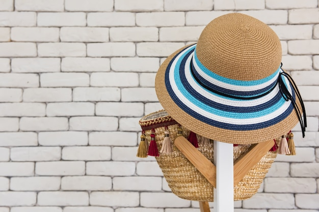 Hat and bag on the background of a white brick wall