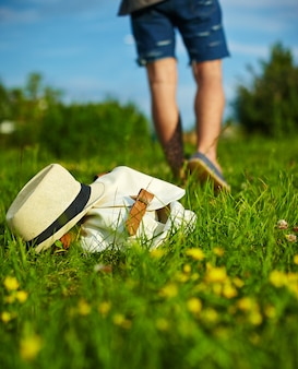 Hat and bag lying in the park in summer green bright colorful grass