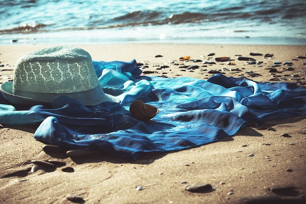 Hat and beach tunic on the beach with the seashore