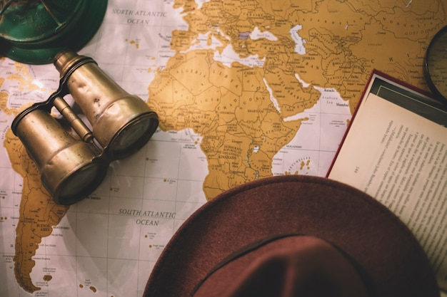 Hat and binoculars on map