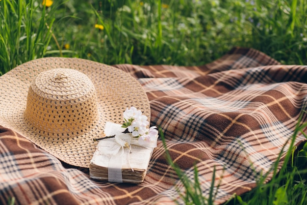 Hat and a book lie on a blanket during a picnic in a blooming spring apple orchard
