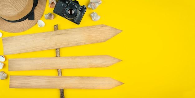 帽子、カメラ、貝殻、木製の門は黄色の背景に平らに横たわっていた