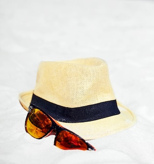 Hat and colorful sunglasses on summer beach white sand near blue ocean