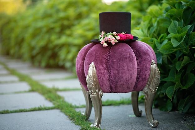 Шляпа цилиндра украшена цветами роз на декоративном фиолетовом пуфе.
