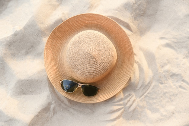 Hat fasion and sunglasses accessories on sandy beach