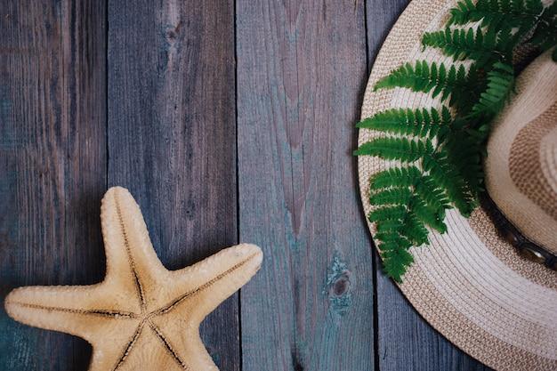 A hat, a fern leaf, a starfish, sea shells on the wooden background