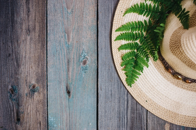 A hat, a fern leaf on the wooden background, copy space
