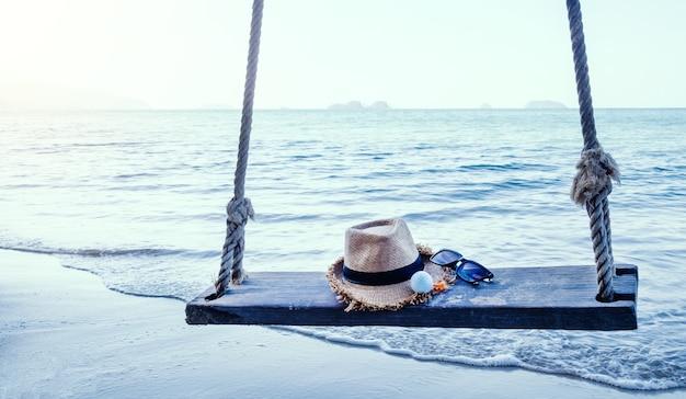 Мяч для гольфа шляпы и очки на качелях на песчаном пляже с морем на заднем плане.