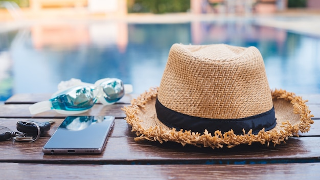 The hat is placed at the wooden table side the swimming pool with smartphone and goggle