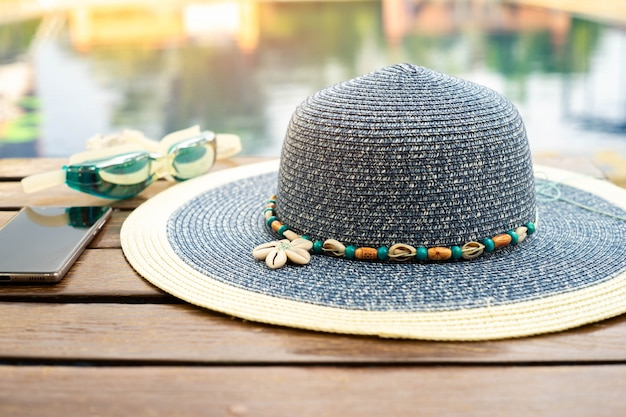 The hat is placed at the wooden table side the swimming pool with smartphone and goggle.