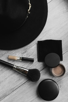 Hat, makeup brush and powder on light wooden background