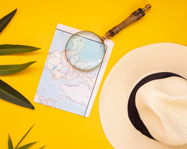 Hat map and magnifying glass on yellow wall, travel concept