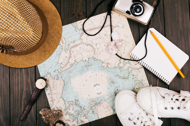 Hat, map, notebook, camera, watch and keds lie on a travel map